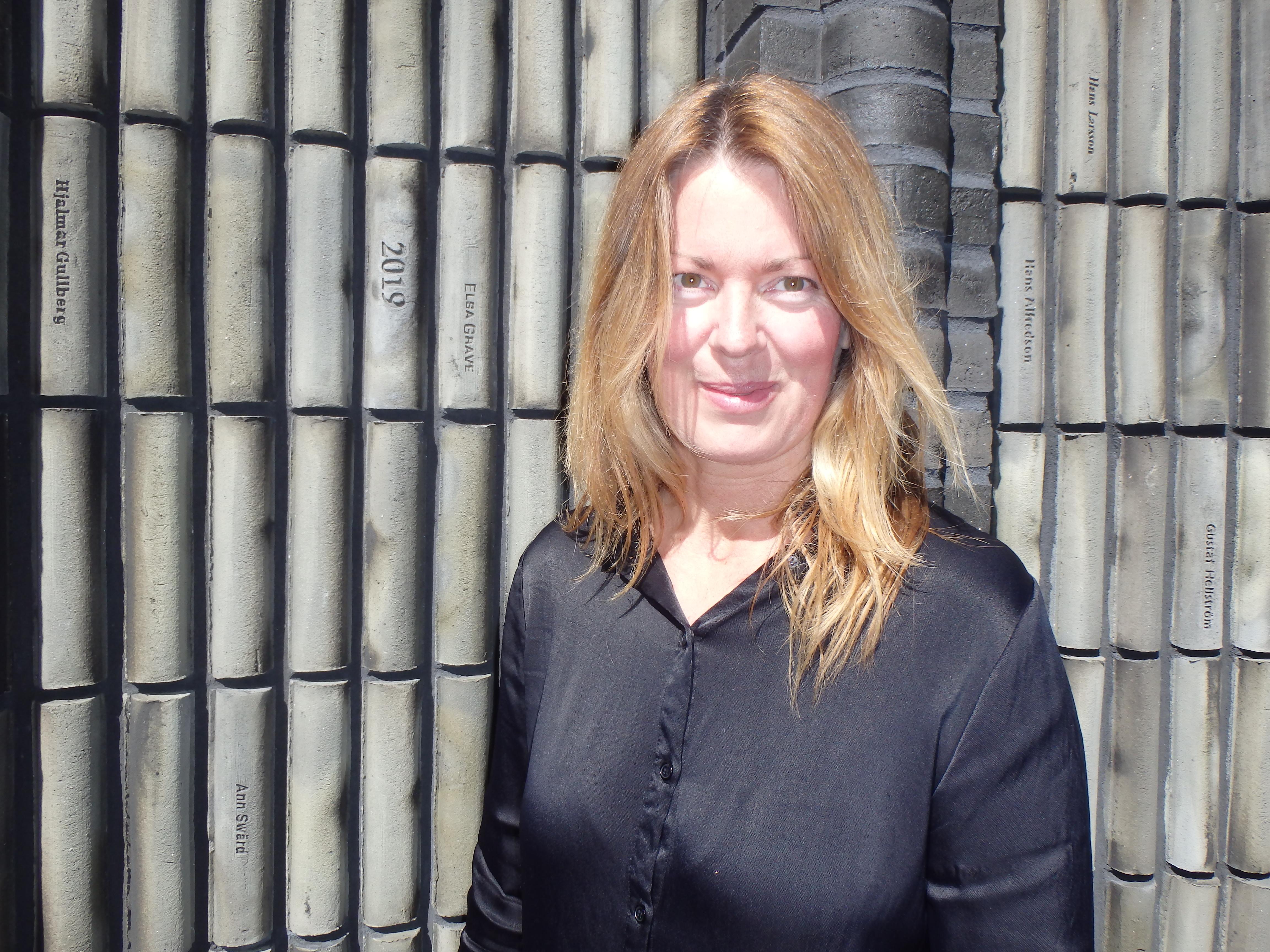 Anne Swärd bredvid boken med hennes namn på ryggen - Foto: Belinda Graham